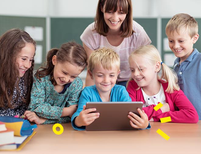 dzieci z nauczycielką korzystające z tabletu w szkole