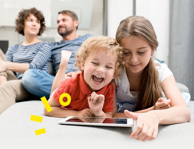 dzieci grające w grę edukacyjną z użyciem tabletu, w tle rodzice